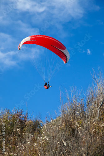 Red paraglider flying in blue sky.