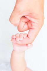 baby hand holding adult finger