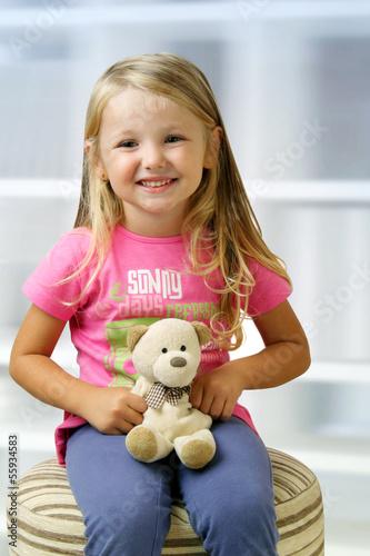 Bambina seduta in relax con il suo peluche