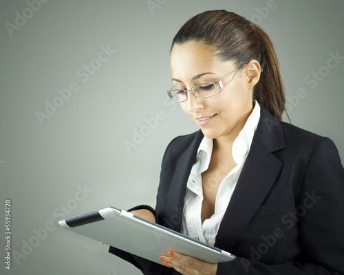 Smiling woman holding a tablet computer over grey background