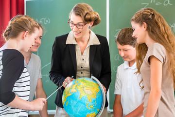 Lehrer unterrichtet Schüler einer Klasse in Erdkunde in der Schu