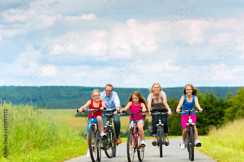 Family cycling in summer in rural landscape