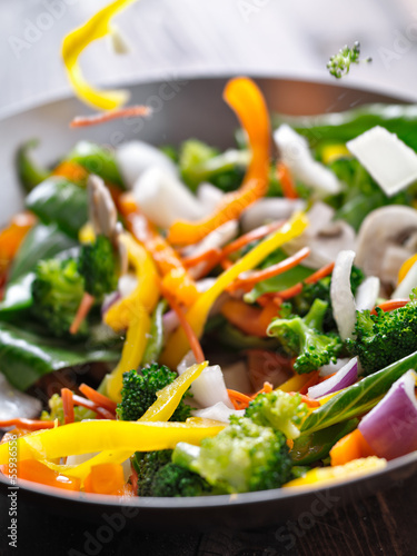 vegetables falling into a stir fry wok.