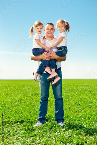Happy family in outdoor park  at sunny day. Dad and two daughter