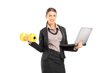 Busy businesswoman holding a laptop and lifting a dumbbell