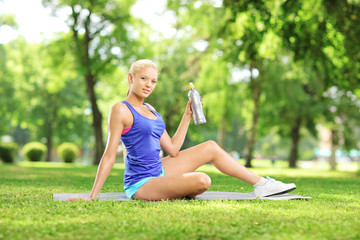 Female athlete resting after excericise holding a bottle in park