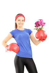 Female athlete wearing boxing gloves and holding flowers