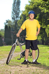 Mature man in sportswear next to his bike