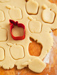 Apple shaped cookie cutter on raw cookie dough