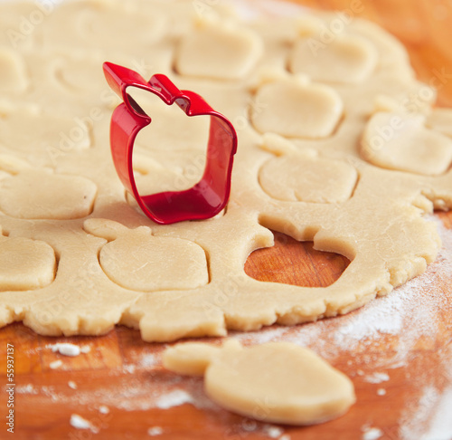 Apple shaped cookie cutter on raw cookie dough. Selective focus