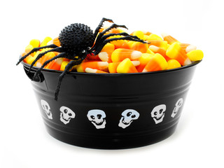 Halloween bowl filled with candy corn and toy spider