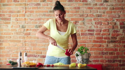 Woman in kitchen showing how to slice, prepare pepper