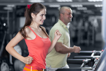 Sportive woman and man are jogging treadmill