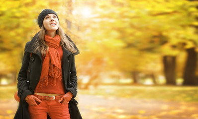 A young brunette woman in warm clothes in an autumn park