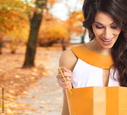 A young brunette woman opening a shopping bag in a park