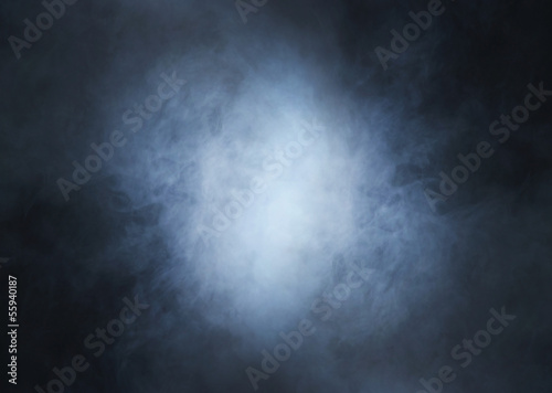 Colorful smoke on a dark background with light in the center