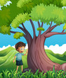 A young boy beside the huge tree