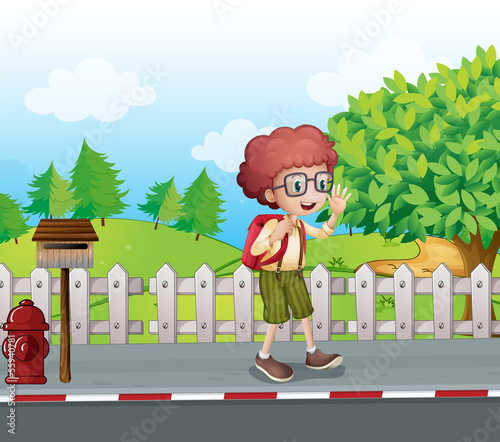 A boy with a backpack walking near the mailbox