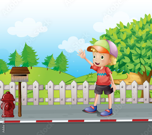 A young boy waving near the mailbox at the road