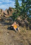 Playful little boy sitting waiting on a mountain