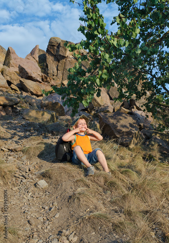 Playful little boy sitting waiting on a mountain