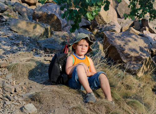 Little boy sitting on the ground at the mountains
