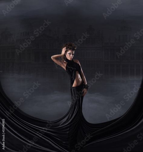 A young and sexy brunette woman posing in a long dark dress