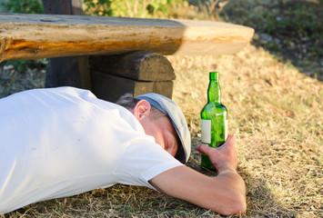 Drunk man sleeping on the ground in summer
