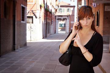 junge Frau mit mobilen Telefon wartet