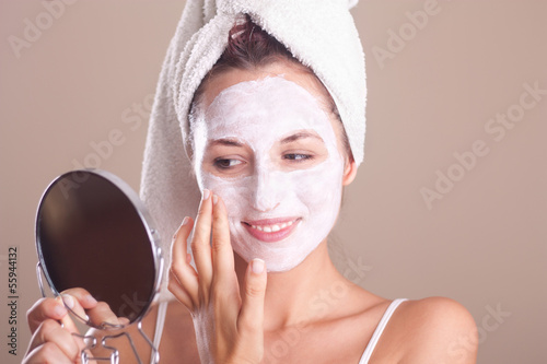 young girl applying  mask on her face and looking in the mirror