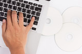 laptop and compact disc with hand
