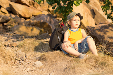 Little boy resting with his rucksack