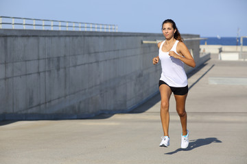 Attractive woman running on the asphalt