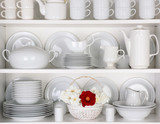White Plates in Cupboard With a Basket of Roses