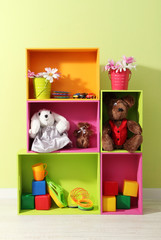 Bright shelves of different colors with toys on wall background