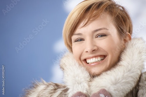 Portrait of happy young woman in fur coat