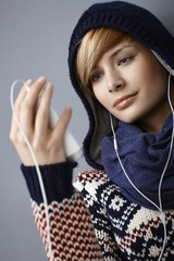 Hooded young woman listening music