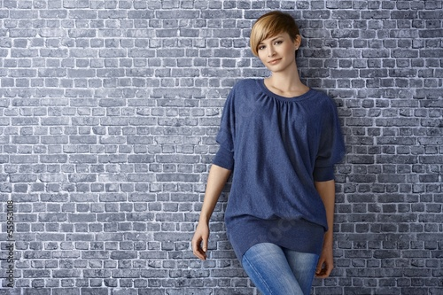 Casual young woman leaning to wall