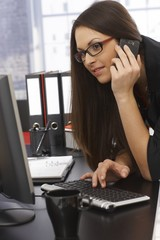 Office photo of woman with mobile and computer