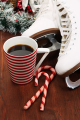Figure skates with cup of coffee on table close-up