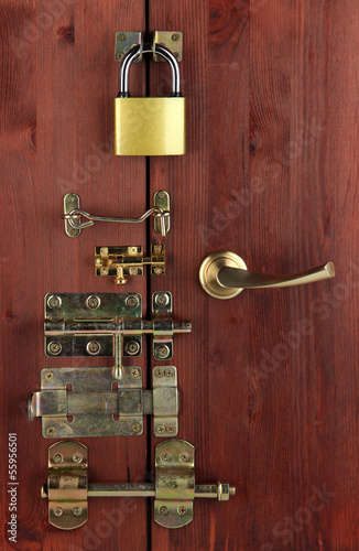 Metal bolts, latches and hooks in wooden door close-up