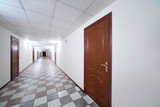 Long bright hallway with wooden doors