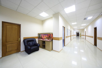 Light white corridorswith doors to offices and aquarium