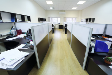 Empty places of work separated by partition with desktops