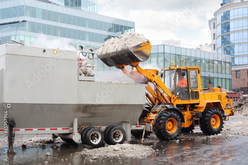 Bulldozer loads snow to truck for snow melting on street in city