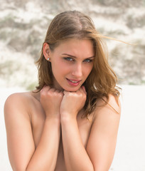 Topless young woman covering her breasts by hands