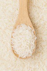 Uncooked white rice on wooden teaspoon