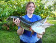Successful angler woman with a big Northern Pike.