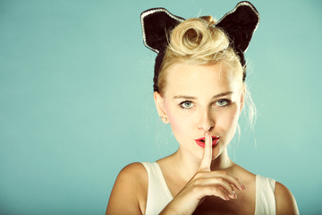 Pin up girl finger near mouth silence gesture