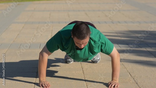 Young man doing push ups and clapping